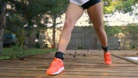Piernas femeninas delgadas en las zapatillas de deporte que sentar-UPS por la piscina, cámara lenta almacen de video