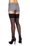 Piernas femeninas delgadas largas en medias y zapatos negros fotos de archivo