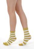 Piernas femeninas elegantes en calcetines rayados Imagen de archivo libre de regalías