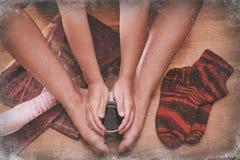 Piernas femeninas en calcetines con una taza de coffe con el invierno de la ventana Fotografía de archivo