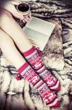 Piernas femeninas en calcetines de la Navidad con un libro y una taza de café Imágenes de archivo libres de regalías