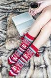 Piernas femeninas en calcetines de la Navidad con un libro y una taza de café Imagenes de archivo