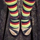 Piernas femeninas en calcetines rayados en estilo del vintage Foto de archivo