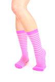 Piernas femeninas en calcetines rayados rosados Imagenes de archivo