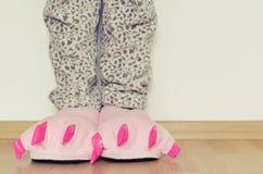 Piernas femeninas en deslizadores rosados lindos del pie del monstruo Foto de archivo