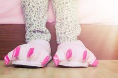 Piernas femeninas en deslizadores rosados lindos del pie del monstruo Imagen de archivo libre de regalías