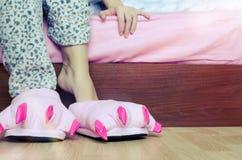 Piernas femeninas en deslizadores rosados lindos del pie del monstruo Foto de archivo libre de regalías