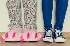 Piernas femeninas en deslizadores y zapatillas de deporte Fotografía de archivo libre de regalías