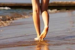 Piernas femeninas en el movimiento en arena de mar mojada Fotos de archivo