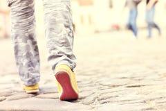 Piernas femeninas en la pavimentación de bloques Imagen de archivo libre de regalías