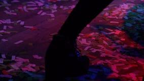 Piernas femeninas en las botas negras que bailan en el partido, clubber disfrutando de la música, celebración metrajes