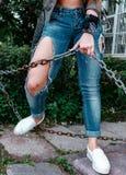 Piernas femeninas en los vaqueros rasgados, primer, muchacha que sostiene una cadena oxidada Imagen de archivo libre de regalías