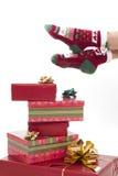 Piernas femeninas en medias de la Navidad contra blanco Fotos de archivo libres de regalías
