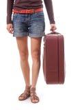 Piernas femeninas en pantalones cortos y maleta a disposición Fotos de archivo