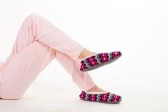 Piernas femeninas en pantalones y deslizadores de pijama Foto de archivo libre de regalías