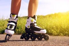 Piernas femeninas en patines en línea en la acción al aire libre el día soleado Imagen de archivo