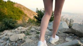 Piernas femeninas hermosas de largo delgadas en las zapatillas de deporte que caminan en Rocky Road And Stops At el top de la mon metrajes