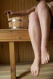 Piernas femeninas hermosas en sauna, accesorios del baño Fotos de archivo libres de regalías