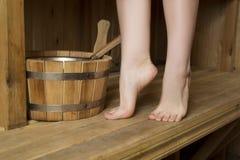 Piernas femeninas hermosas en sauna, accesorios del baño Imagen de archivo