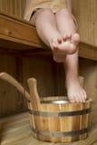 Piernas femeninas hermosas en sauna, accesorios del baño Imagenes de archivo