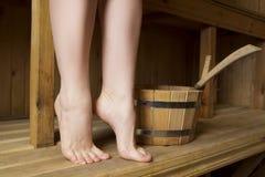 Piernas femeninas hermosas en sauna, accesorios del baño Imagen de archivo libre de regalías