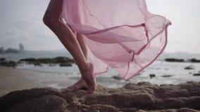 Piernas femeninas hermosas en un vestido rosado que se convierte largo en la costa en las piedras Primer 4K metrajes