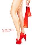 Piernas femeninas hermosas, manera roja, haciendo compras Foto de archivo libre de regalías