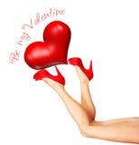 Piernas femeninas hermosas que llevan a cabo el corazón Foto de archivo libre de regalías