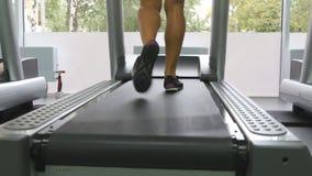 Piernas femeninas que caminan en la rueda de ardilla en gimnasio Mujer joven que ejercita durante entrenamiento cardiio Pies de m almacen de video