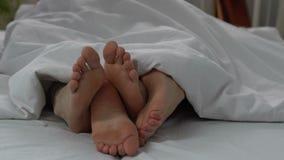 Piernas femeninas y masculinas en la cama, par feliz que hace el amor por la mañana, primer metrajes