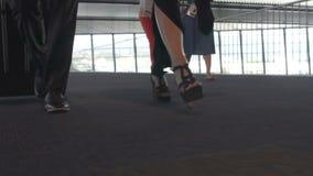 Piernas femeninas y masculinas que caminan en piso alfombrado del aeropuerto con la maleta, salida metrajes