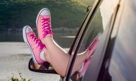 Piernas fuera de la ventanilla del coche por el lago Imágenes de archivo libres de regalías