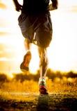 Piernas fuertes del hombre joven del rastro que corre en la puesta del sol asombrosa del verano en deporte y forma de vida sana foto de archivo