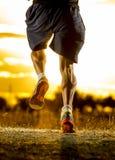 Piernas fuertes del hombre joven del rastro que corre en la puesta del sol asombrosa del verano en deporte y forma de vida sana foto de archivo libre de regalías
