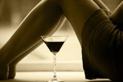 Piernas hermosas de la muchacha y un vidrio de la bebida fotografía de archivo libre de regalías