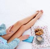 Piernas hermosas de la mujer en la opinión superior de la cama Fotografía de archivo