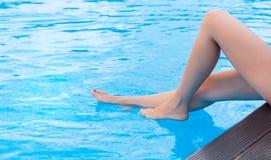 Piernas hermosas en piscina Foto de archivo libre de regalías