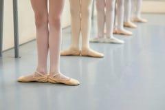 Piernas jovenes de las bailarinas en la posición básica Foto de archivo