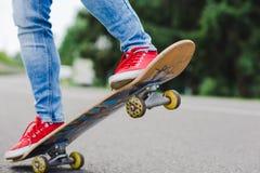 Piernas jovenes del skater que montan en el monopatín en ciudad Fotografía de archivo libre de regalías