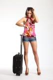 Piernas largas atractivas de la mujer que esperan con la maleta Foto de archivo libre de regalías