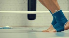 Piernas masculinas del boxeador que saltan en cuerda que salta mientras que entrenamiento cardiio en el anillo en club de la luch almacen de video