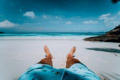 Piernas masculinas del fondo de las vacaciones del viaje con cortocircuito de la nadada en la playa tropical de la arena blanca d foto de archivo libre de regalías