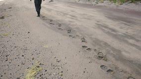 Piernas masculinas en las botas que caminan en Sandy Beach Leaving Behind Footprints 4K almacen de video