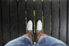 Piernas masculinas en pantalones cortos y zapatos blancos en un puente de madera, visión superior Imagen de archivo libre de regalías