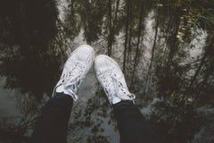 Piernas masculinas en zapatillas de deporte contra el agua con la reflexión de árboles Imágenes de archivo libres de regalías