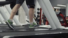 Piernas masculinas que corren en la rueda de ardilla en gimnasio Ciérrese para arriba de los pies que corren en las ruedas de ard almacen de video