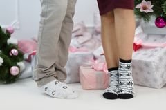 Piernas masculinas y femeninas en calcetines calientes con los modelos de copos de nieve y de pingüinos indoor Imagenes de archivo