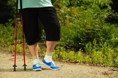 Piernas mayores activas en nordic de las zapatillas de deporte que camina en un parque Fotos de archivo libres de regalías