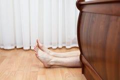 Piernas melenudas descubiertas después de la cama Foto de archivo libre de regalías