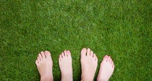 Piernas mezcladas pares que se unen cercanas en hierba Imagen de archivo